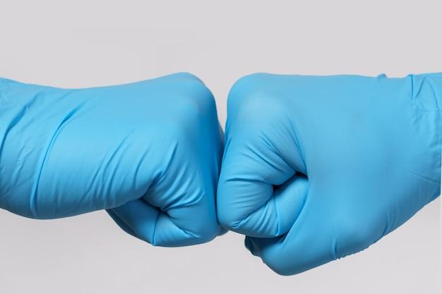 一緒に働こう!コロナウイルスとの戦い。拳をぶつけるジェスチャーをする 2 人の医療従事者。