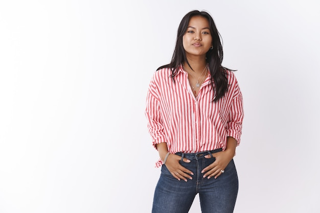 Let talk business language. portrait of good-looking confident and stylish young 20s woman in striped blouse holding hands on pockets looking self-assured at camera, showing who boss