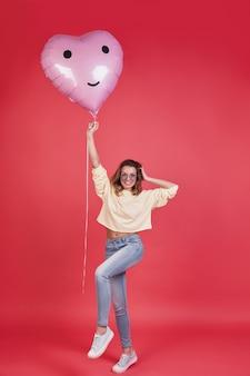 Пусть вечеринка началась! полная длина привлекательной молодой улыбающейся женщины, держащей воздушный шар в форме сердца и держащей руку в волосах, стоя на розовом фоне