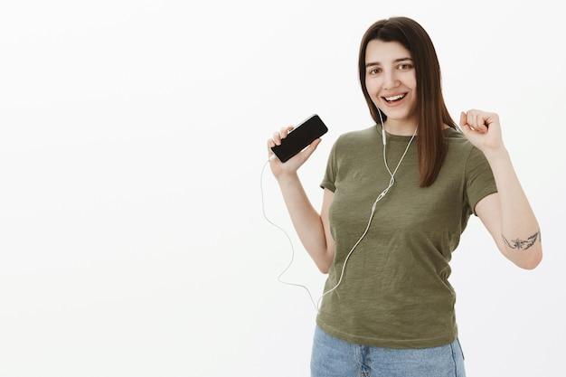 ダンスフロアを振ってみましょう。灰色の壁の上でスマートフォンアプリを使用してイヤホンで音楽を聴いて踊る喜びと自信を持って手を上げる、うれしそうで自信のある見栄えの良い明るい20代女性