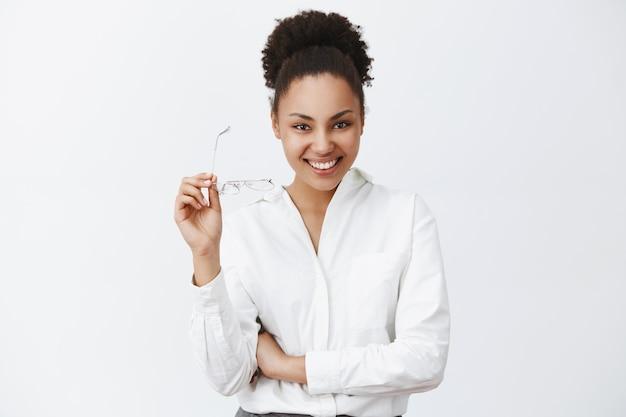ビジネスについてお話しましょう。黒い肌と巻き毛の魅力的で自信に満ちたフレンドリーな成功した女性起業家、メガネを脱いで、スマートでクリエイティブな外観を凝視