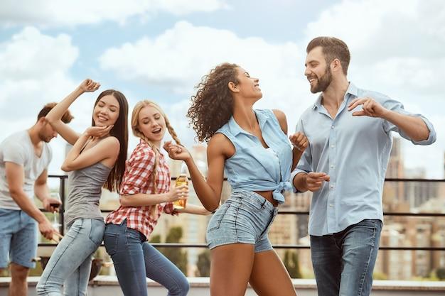 幸せで遊び心のある若者のグループが踊って楽しんでいるダンスをしましょう