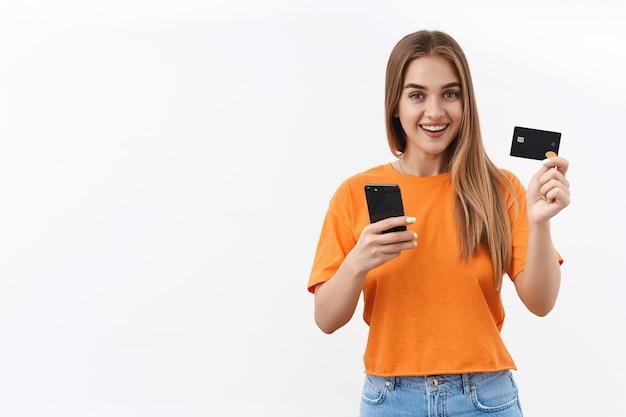 온라인 쇼핑을 해보자. 코비드-19 자가 격리에 앉아 신용 카드와 휴대 전화를 사용하여 음식 배달 비용을 지불하는 쾌활한 금발 소녀의 초상화