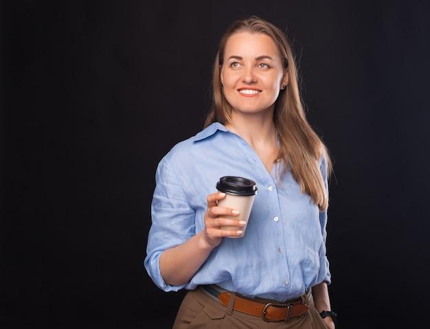 커피 한 잔을 마실 수 있게 하고, 공식적인 옷을 입은 젊은 비즈니스 여성이 종이컵을 들고 웃고 있다