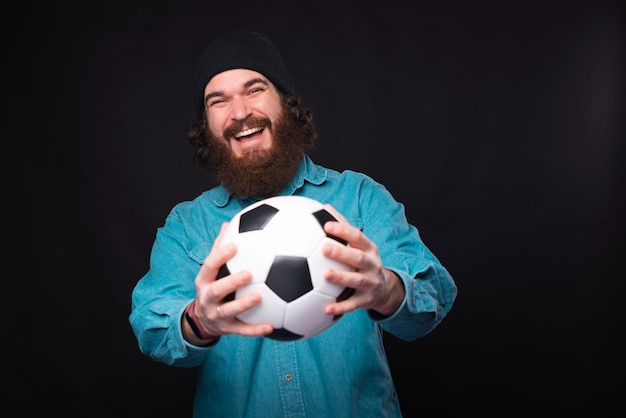 Lets go play football. happy bearded man holding soccer ball and looking