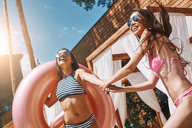 一緒に行こう水着姿の2人の遊び心のある若い女性が手をつないで笑っている