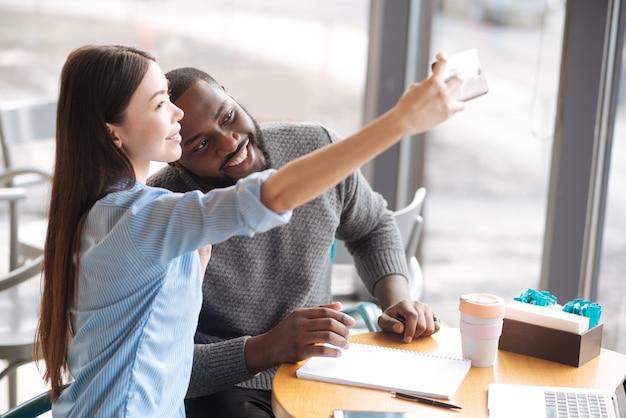 投稿しましょう。大きな窓の近くに座っている間、彼女の男性の友人と自分撮りをしているかなり若い女性。