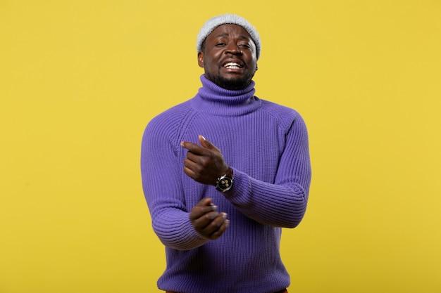 歌いましょう。黄色い壁にポーズをとっている間彼の顔に笑顔を保つ陽気な男性の人