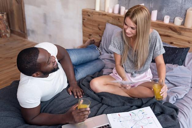 一日を始めましょう。ベッドに横たわっている間にジュースを飲み、文書を発見する甘い国際的な若いカップル。