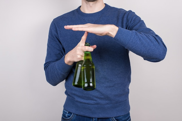 Lets stop and have rest concept. cropped closeup photo of confident handsome football fan give pause holding two bottles in hands invine on short break isolated grey background