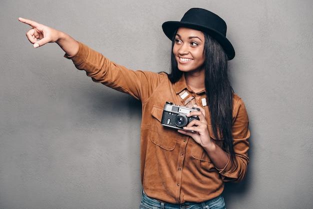 Давай сфотографируемся там! красивая веселая молодая африканская женщина держит камеру в стиле ретро