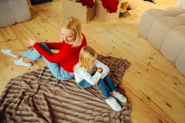 Lets talk. sad preschooler leaning on knees while being angry with mother
