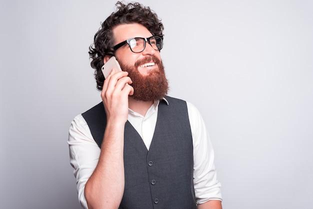 あなたと話しましょう、誰かと電話で話しているスーツを着た魅力的でハンサムなひげを生やした男
