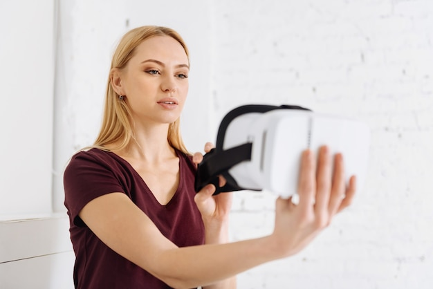 Lets try. delighted female person keeping smile on her face and stretching arm while going to wear mask for virtual vision