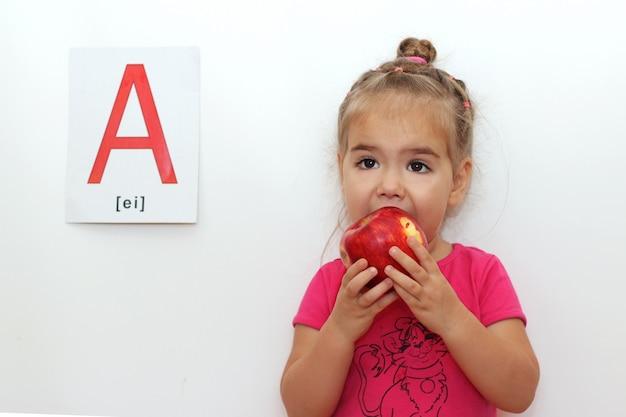 Буква «а» как яблоко. милая маленькая девочка ест свежее красное яблоко
