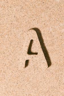夏のアルファベットのビーチ砂の概念で分離された砂の文字a