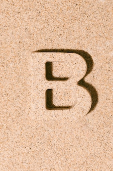 Letter b of the sand isolated on the beach sand concept of summer alphabet