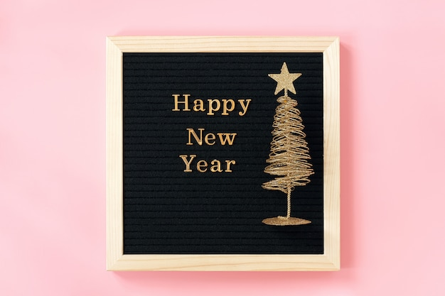 Letter board with golden text happy new year and shiny christmas tree on pink wall