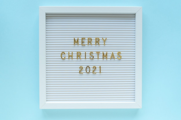 Letter board with merry christmas 2021 greeting, decorations on blue pastel backdrop. christmas composition. top view