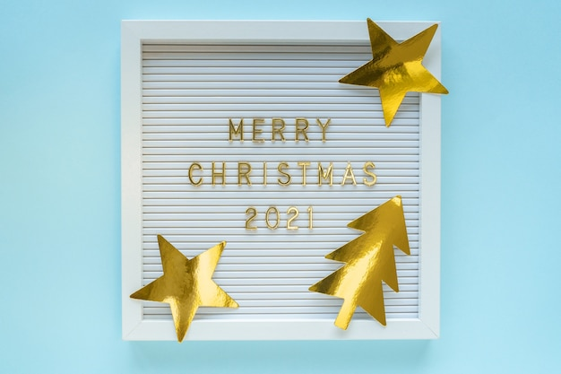 Letter board with merry christmas 2021 greeting, decorations on blue pastel girly backdrop. christmas composition. flat lay, from above