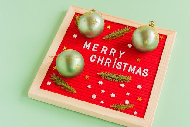 メリークリスマス2022挨拶、緑の背景のレターボードの挨拶の引用とレターボード。フラットレイ、上から、最小限のスタイル。