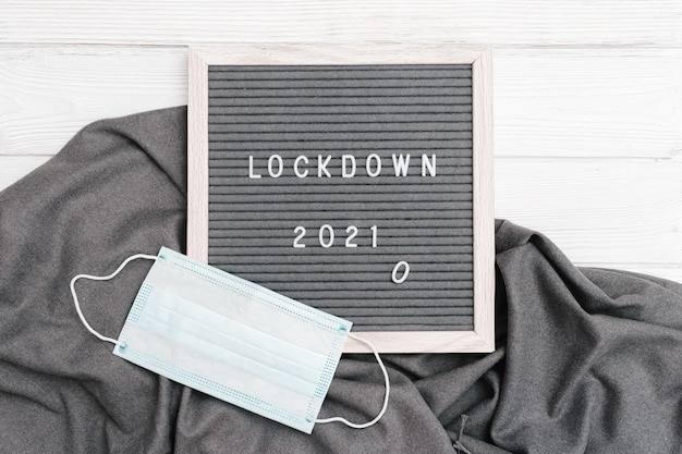 Letter board with message text lockdown 2021 and protective face mask.  social media content.
