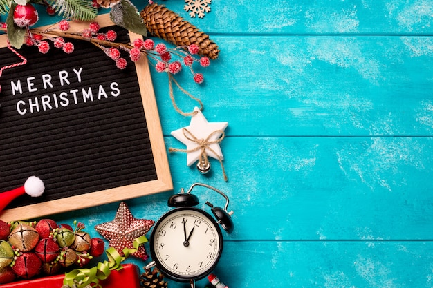 Letter board with words merry christmas, vintage clock and decorations on blue wooden table. winter christmas celebration concept. free space for your text