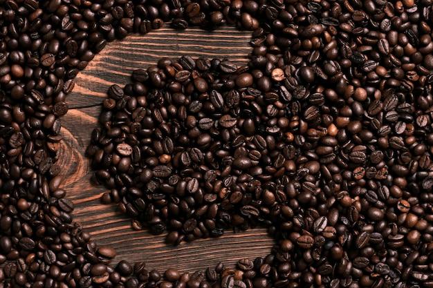 木製のテーブルにコーヒー豆と文字cの碑文。上面図。スペースをコピーします。静物。モックアップ。フラットレイ