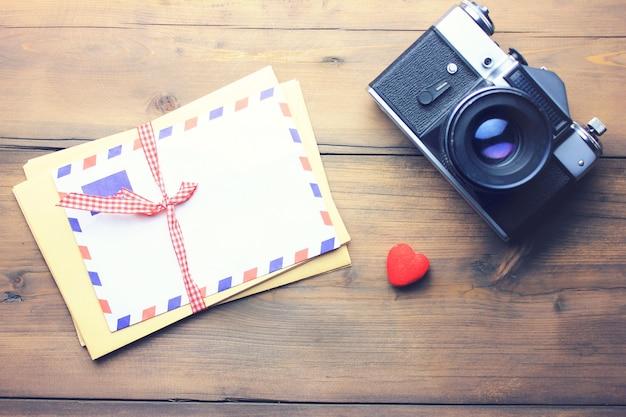 나무 테이블 배경에 편지, 카메라 및 심장