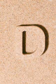 夏のアルファベットのビーチ砂の概念で分離された砂の文字d