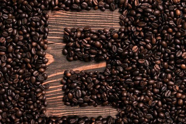 木製のテーブルにコーヒー豆と文字eの碑文。上面図。スペースをコピーします。静物。モックアップ。フラットレイ