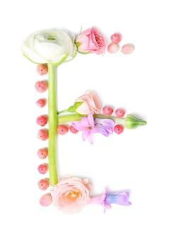白い背景の上に花とハーブで作られた文字e