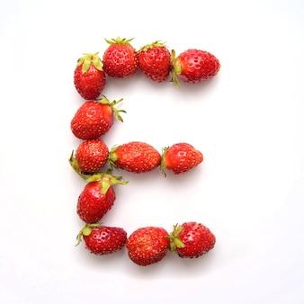 Буква e английского алфавита красной свежей клубники на белом фоне