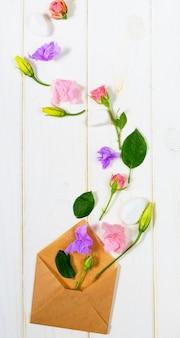 Письмо, конверт и подарок в эко бумаги на белом фоне. свадебные приглашения или любовное письмо с розовыми розами.