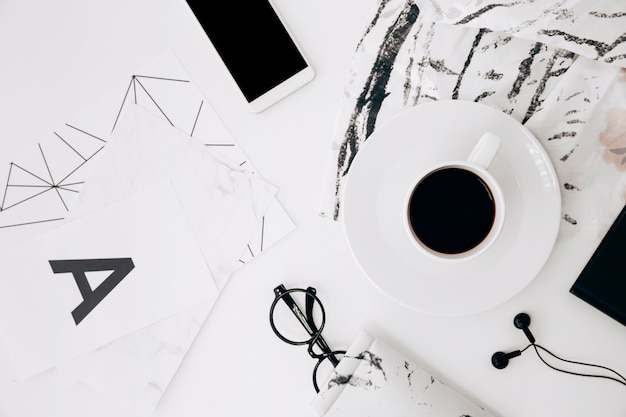 Letter a; eyeglasses; smartphone; earphone; coffee cup on white desk