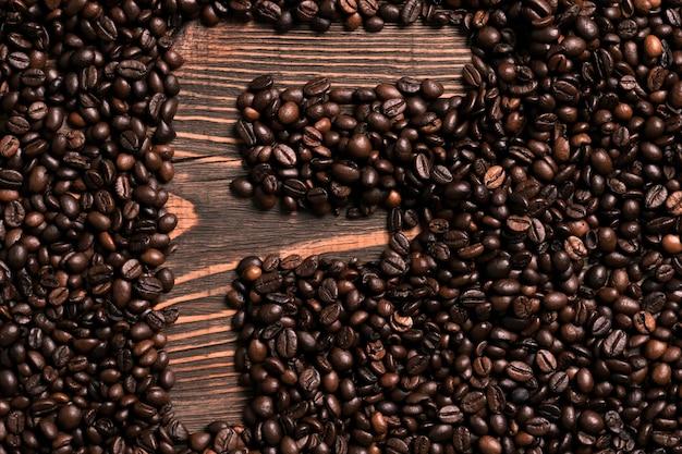 木製のテーブルにコーヒー豆と文字fの碑文。上面図。スペースをコピーします。静物。モックアップ。フラットレイ
