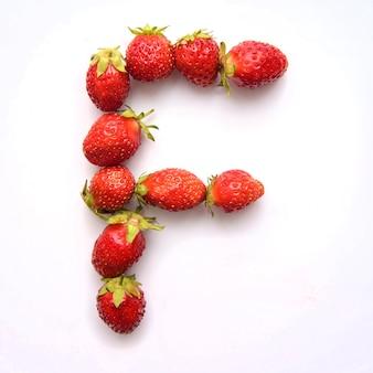 Буква f английского алфавита красной свежей клубники на белом фоне