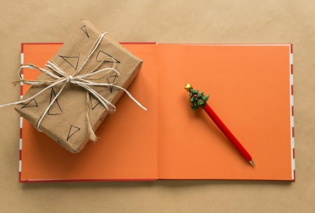 Письмо деду морозу, новогодняя ручка и новогодний блокнот, лежат на столе