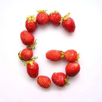 Буква g английского алфавита красной свежей клубники на белом фоне