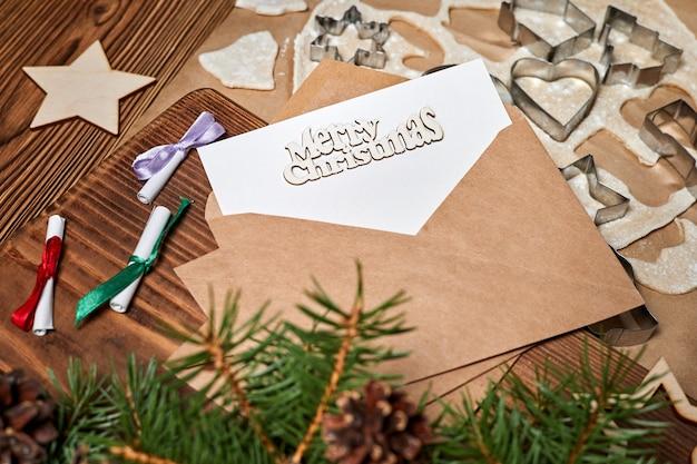 Письмо в конверте с надписью merry christmas на фоне сырого рождественского печенья