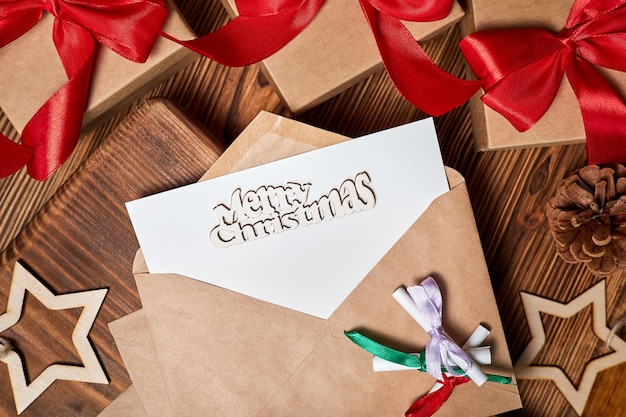 Письмо в конверте с надписью merry christmas на фоне рождественских подарочных коробок