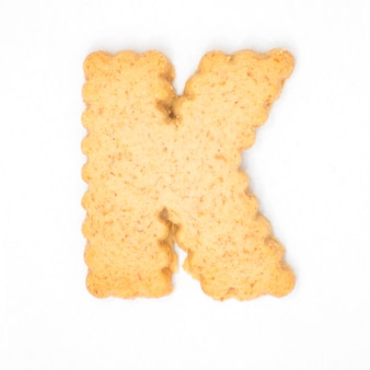 Letter k made of cracker cookie isolated on white background