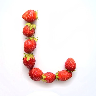 Letter l of the english alphabet of red fresh strawberries on white background