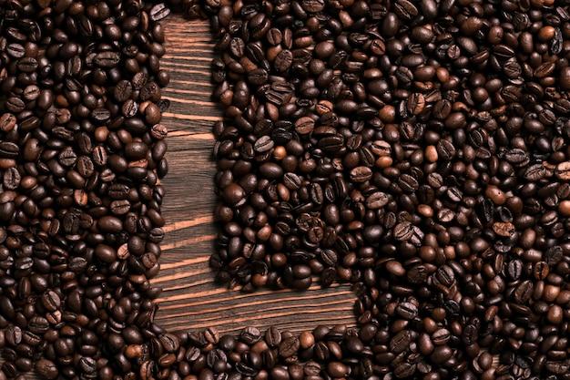 木製のテーブルにコーヒー豆と文字lの碑文。上面図。スペースをコピーします。静物。モックアップ。フラットレイ