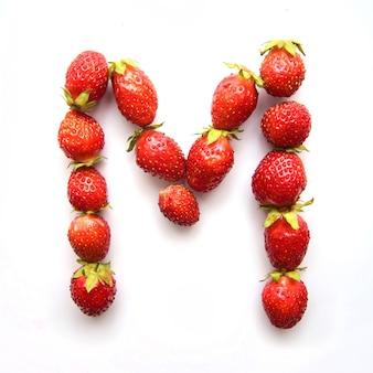 Буква m английского алфавита красной свежей клубники на белом фоне
