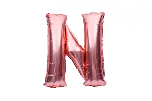 Letter n made of rose golden inflatable helium balloon isolated on white. gold pink foil balloon font part of full alphabet set of upper case letters.
