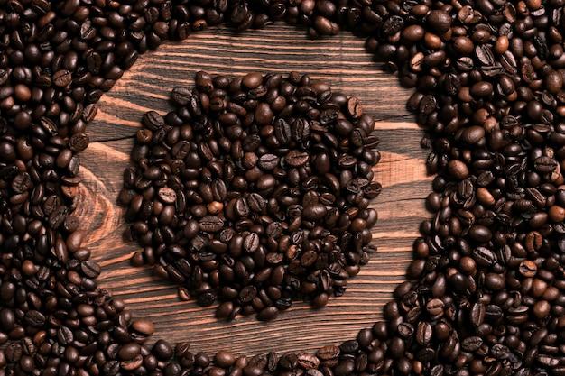 木製のテーブルにコーヒー豆と文字oの碑文。上面図。スペースをコピーします。静物。モックアップ。フラットレイ