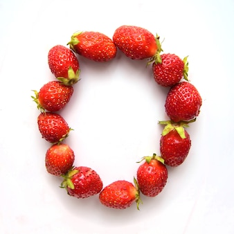 Буква o английского алфавита красной свежей клубники на белом фоне