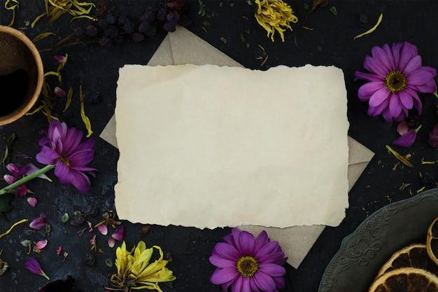 Wilted 꽃, 커피 한 잔, 빈티지 접시 사이의 봉투에 편지.