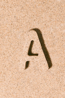 Letter a of the sand isolated on the beach sand concept of summer alphabet